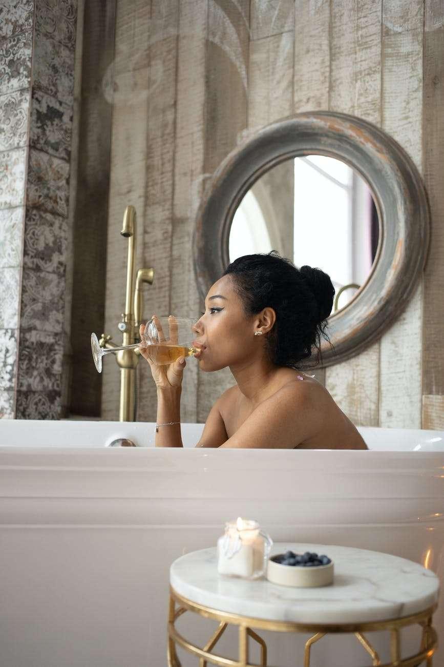 ethnic woman drinking white wine in bathtub